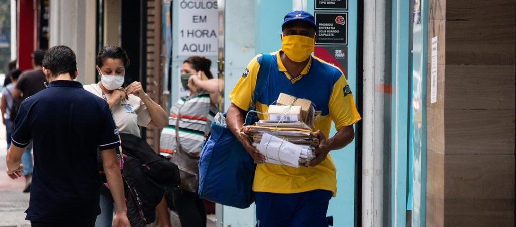 People are in the streets during COVID-19 pandemic wearing masks; a postman is in the front of the picture with small packages in his hands.
